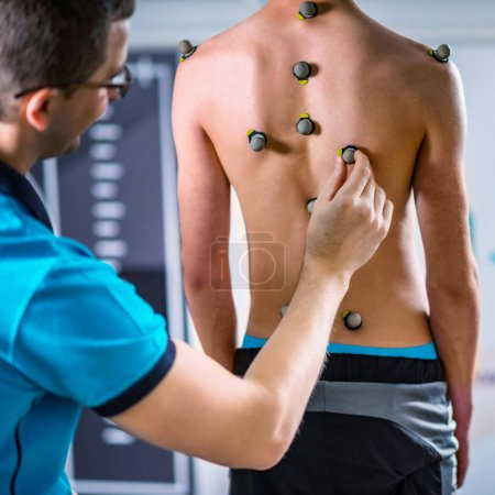 Physical Therapist  Placing  boy with marking balls for posture analysis at health club