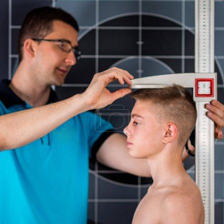 Foto de Fisioterapeuta midiendo la altura del adolescente - Imagen libre de derechos