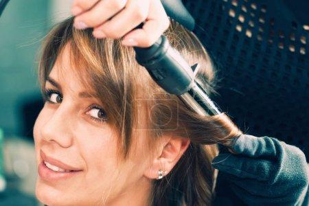 Photo pour Coiffeur cheveux bouclés avec fer à friser - image libre de droit