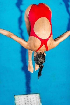 Photo pour Plongeuse, sauter dans la piscine de plongeoir - image libre de droit