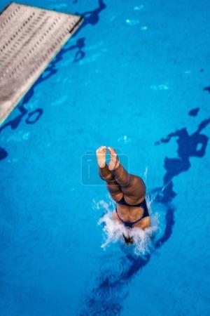 Female diver jumping into the pool from diving board