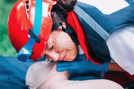Cpr practice of woman on cpr dummy outdoors