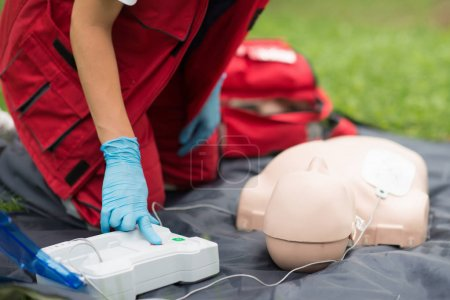 Cpr training of woman on cpr dummy outdoors