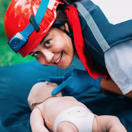 Cpr training of woman on baby dummy outdoors