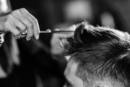 Hair styling man in hairsalon by female hairdresser
