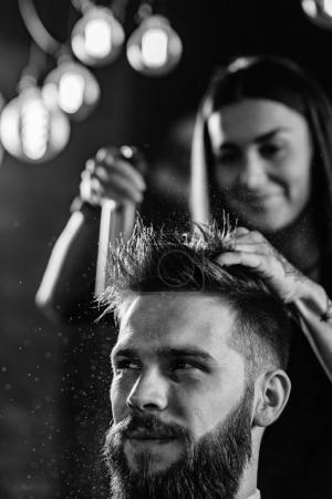 Hair styling man in hairsalon by female hairdresse...