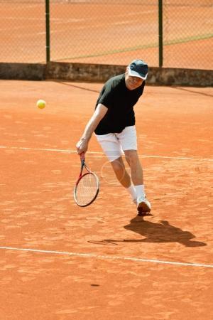 Senior male player hitting ball