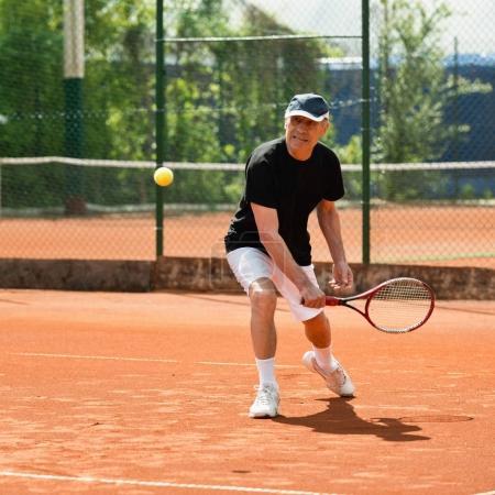 Senior man hitting ball on tennis court