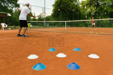 girl with coach Exercising tennis outdoors