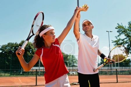 Female serving tennis ball on tennis class