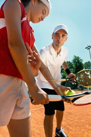 girl playing tennis with coach