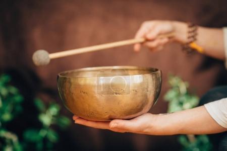 woman hands holding Tibetan singing bowl