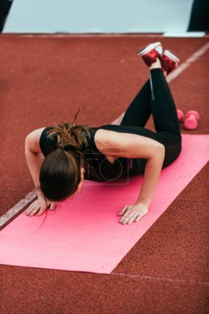 Young woman doing push ups on competition outdoors