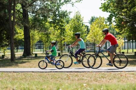 Cheerful family biking together in park