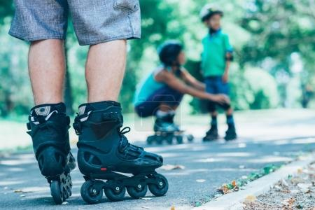 Father's Roller skaters in focus with mother and son in background