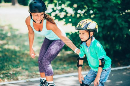 Mother teaching son roller skating in pair