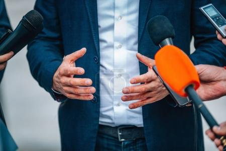 journalists interviewing businessman on press conference