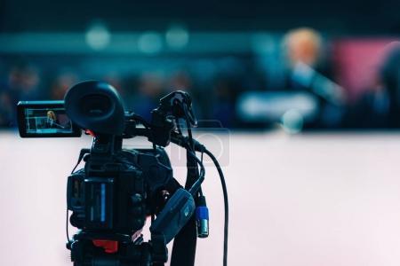 Video camera recording press conference...