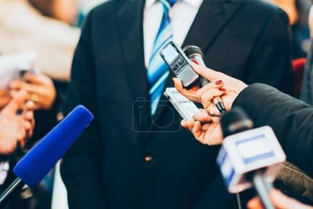 Journalists interviewing business person on public event
