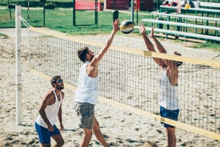 Male team playing beach volleyball