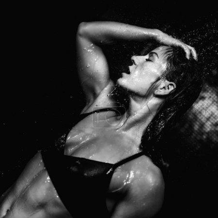 Photo pour Femme sous gouttes d'eau. Douche, fond noir . - image libre de droit
