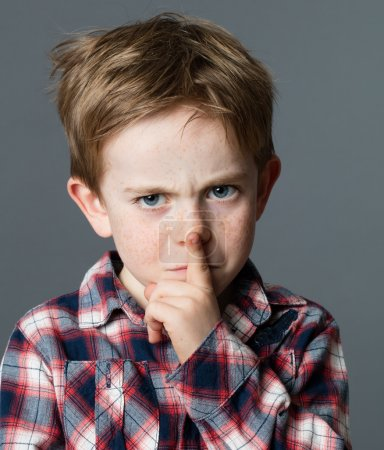 unhappy young boy with finger on lips for secret gesture
