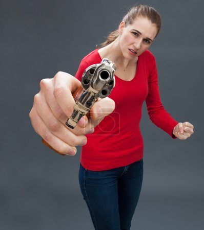 anxious beautiful young woman with gun expressing violence and intimidation
