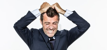 enraged young businessman pulling his hair out for exasperation