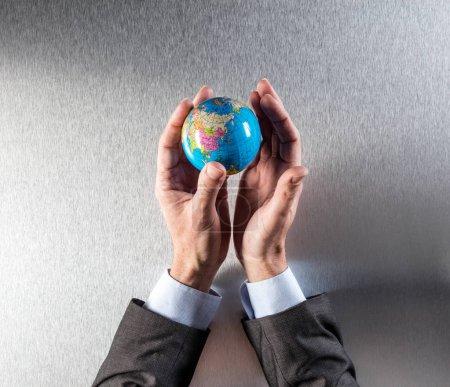Photo pour Homme d'affaires vert tenant la terre entre ses mains pour le concept de responsabilité humaine et mondiale et la gestion de l'environnement international, ci-dessus vue - image libre de droit