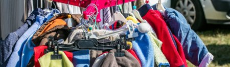 Used child and baby clothes displayed on rack at o...