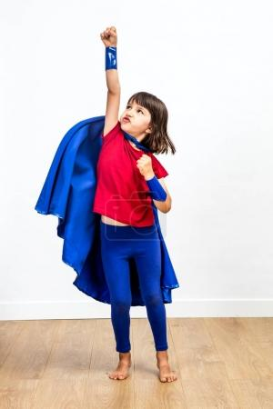 Photo for Motivated super hero kid showing strength and imagination, playing with a powerful arm raised reaching success and future over white background and wooden floor, indoors - Royalty Free Image