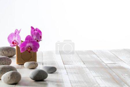 Photo pour Beauté naturelle, hygiène, douche ou lavage durable à la lessive avec cailloux zen, orchidées et savon traditionnel à l'huile d'olive de Marseille, espace de copie en bois - image libre de droit