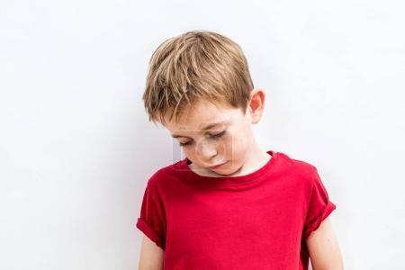 Photo for Disappointed little child looking down expressing solitude, disillusion, sadness or education and parent problems, white background - Royalty Free Image