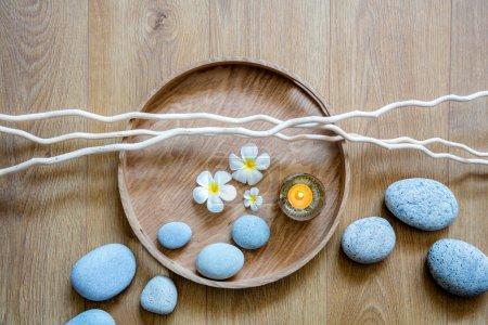 Photo pour Décor de spa pour ayurveda naturel, beauté choyer, bien-être de désintoxication ou massage zen avec un flux de cailloux, bougie, fleurs et brindilles sur plateau rond en bois et fond, vue sur le dessus - image libre de droit