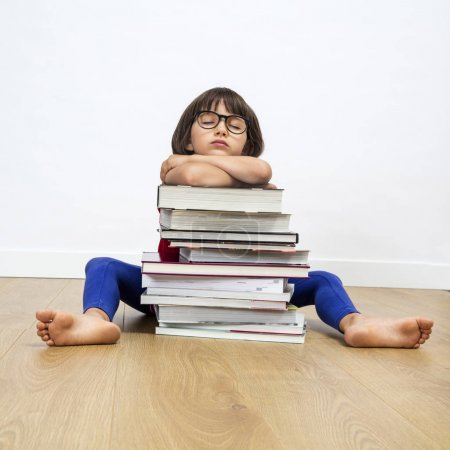 Photo pour Enfant endormi accablé avec des lunettes de ver de bibliothèque dormant sur une pile de livres à la bibliothèque après avoir lu et appris, assis sur le sol en bois - image libre de droit