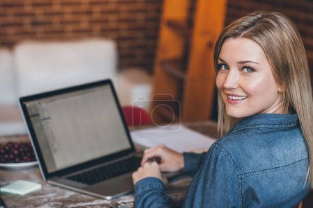 woman looking over shoulder and using laptop