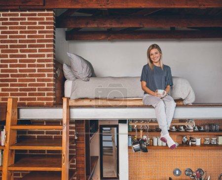 woman in pajamas sitting in bedroom