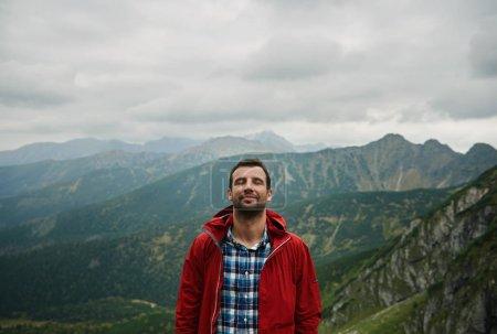 Photo pour Homme avec ses yeux fermés debout au sommet d'une montagne avec un paysage de collines sous un ciel couvert derrière lui tandis que sur le trekking dans le désert - image libre de droit