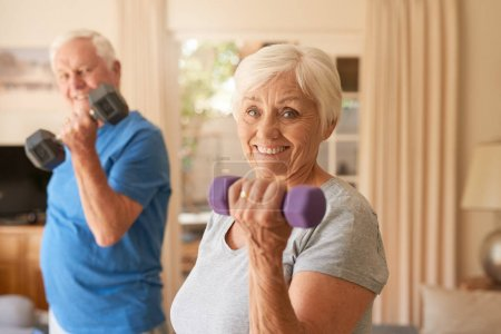 Photo for Portrait of an active senior couple in sportswear smiling and lifting dumbells while exercising together in their living room at home - Royalty Free Image
