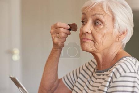 woman applying foundation to cheek