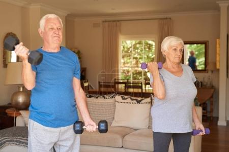 Photo for Active and focused senior couple in sportswear lifting dumbells while exercising together in their living room at home - Royalty Free Image