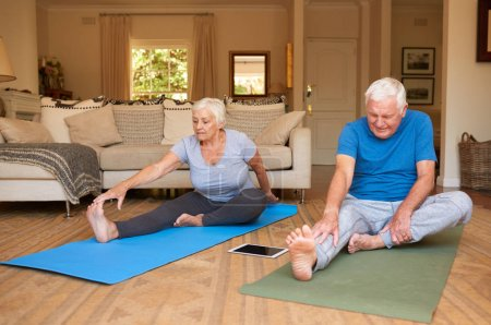 Photo for Active and focused senior couple doing the stretching while practicing yoga together in their living room at home - Royalty Free Image