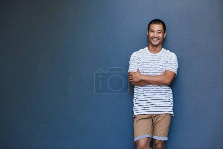 Foto de Retrato de un hombre asiático joven elegantemente vestido sonriente inclinada con los brazos cruzados contra una pared gris exterior - Imagen libre de derechos