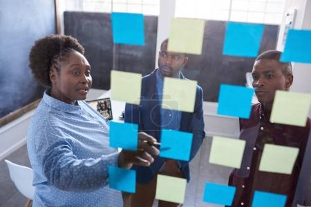 Photo for Three casually dressed African work colleagues planning business together on a glass wall with sticky notes while standing in a modern office - Royalty Free Image