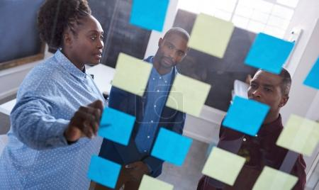 Photo for Three casually dressed African work colleagues brainstorming together with sticky notes on a glass wall while standing in a modern office - Royalty Free Image