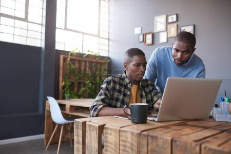 Photo for Two casually dressed young African business colleagues using a laptop and talking together while working at a table in a modern office - Royalty Free Image