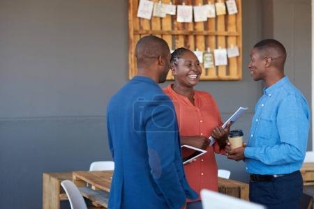Foto de Tres vestidos casualmente con compañeros de trabajo de la oficina africana joven sonriendo y hablando juntos estando en una gran oficina moderna - Imagen libre de derechos