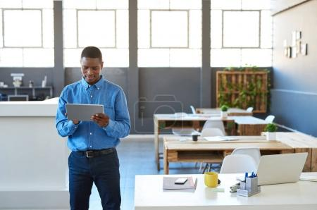 Photo for Focused young African businessman standing confidently in a large bright modern office working online with a digital tablet - Royalty Free Image