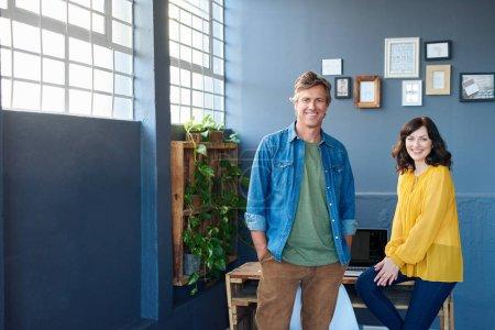 Photo pour Portrait de deux collègues de bureau négligemment habillée, souriant en toute confiance tout en travaillant dans un bureau modern lumineux - image libre de droit