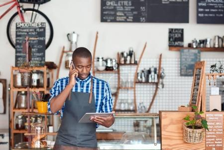 Photo for Young African entrepreneur talking on a cellphone and using a digital tablet while standing in his trendy cafe - Royalty Free Image